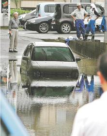 冠水した道路にはまり、立ち往仁生する乗用車=27日16時、気仙沼市田中前