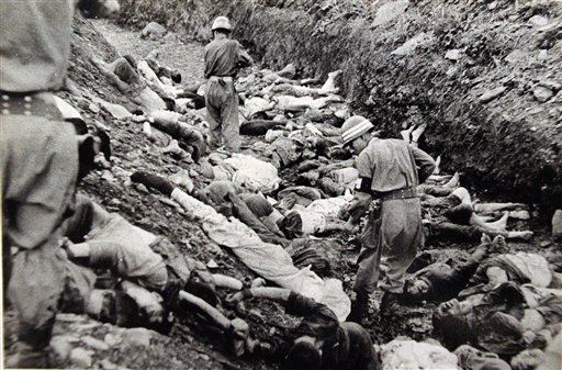 South_Korean_soldiers_walk_among_dead_political_prisoners,_Taejon,_South_Korea