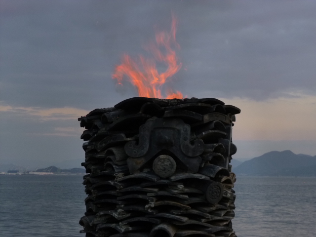 かつて人が住んでいた家の瓦を使い,廃材を燃やします