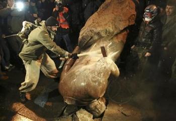 2013-12-09_Russia_Ukraine_キエフで大規模抗議集会 レーニン像倒される_8日、倒されたレーニン像にハンマーを振り下ろすデモ参加者(ロイター)