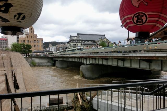 濁流が荒れ狂う鴨川を心配そうに見る京都市民